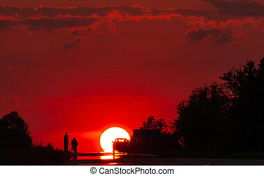Solar disk and silhouettes of car and people against the background of the red sunset sky
