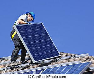 Man installing alternative energy photovoltaic solar panels on roof