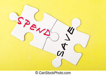 Spend and save words written on two pieces of puzzle