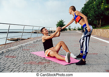 Sportive girl helps a sportsman to get up
