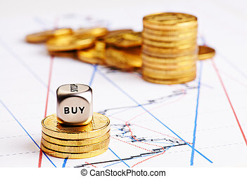 Stacks of coins, dices cube with word BUY and a up trend chart as the background. Successful trading. Selective focus