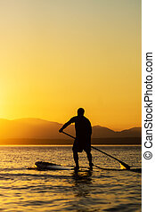 Man paddling stand up paddle board at sunset with mountains in background.
