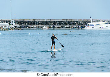 Stand up paddle board man paddleboarding on Peruvian beach standing happy on paddleboard on blue water.