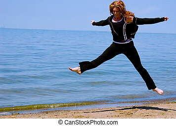 A woman leaps high on the beach