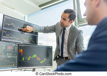 Stock brokers looking at computer screens, trading online.