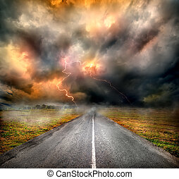 Storm clouds and lightning over highway in the field