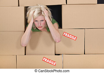 Stressed woman surrounded by boxes
