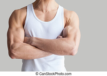Strong and healthy body. Cropped image of muscular man keeping arms crossed while standing isolated on grey background
