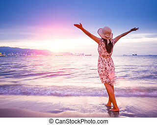 Strong confidence woman open arms under the sunrise at seaside. Summer and travel concept.