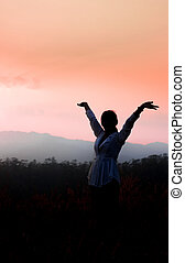 strong confident woman open arms under the sunrise at mountain