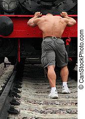 strong shirtless man pushs locomotive