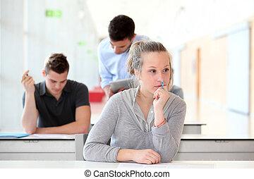 Student passing examination in school classroom