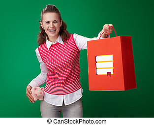 student woman with piggy bank giving shopping bag with books
