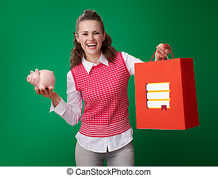 student woman with shopping bag with books and piggy bank