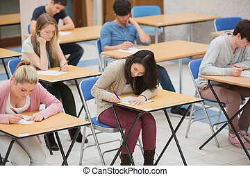 Students writing in the exam hall of the college