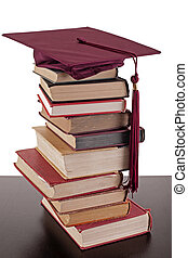 a stack of books on tabletop with a graduation cap on top