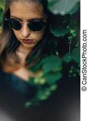 Stylish hipster girl posing at green hop bush, atmospheric moment. Portrait of fashionable cool woman in black sunglasses relaxing in park. Selective focus, creative image. Space for text