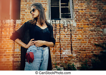 Stylish hipster girl posing in street, atmospheric moment. Fashionable cool woman in black sunglasses and denim jeans standing at old brick building. Space text. Retro effect