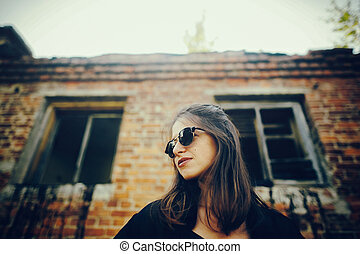 Stylish hipster girl posing in street, atmospheric moment. Fashionable cool woman in black sunglasses standing at old brick building. Selective focus. Space text. Retro effect