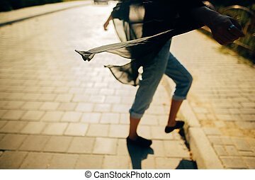 Stylish hipster girl walking in sunny light in street, atmospheric moment. Fashionable cool woman in denim jeans and black shirt relaxing in city. Selective focus. Space for text