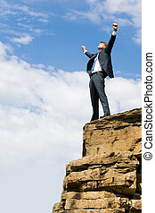 Image of delighted businessman standing on the mount peak with his arms raised