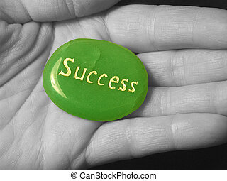 Success stone in a black and white hand.