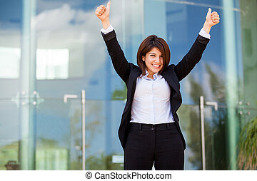 Happy and successful businesswoman raising her arms and celebrating