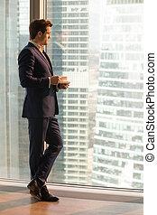 Successful businessman enjoying sunset from office