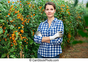 Successful female grower in greenhouse near yellow grape tomatoes