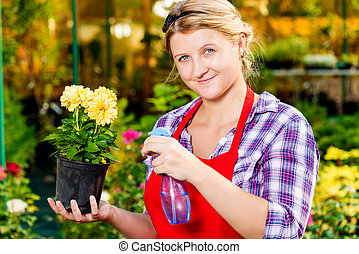 Successful florist with a flower pot in the greenhouse