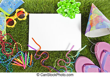 A collection of summer party items on a grass mat with a blank space for text.