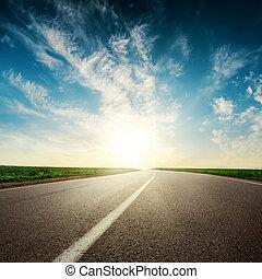 sunset in clouds over asphalt road