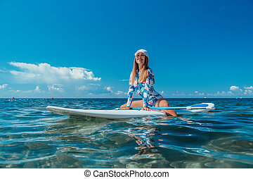 SUP Stand up paddle board. Young woman sailing on beautiful calm sea with crystal clear water. The concept of an summer holidays vacation travel, relax, active and healthy life in harmony with nature.