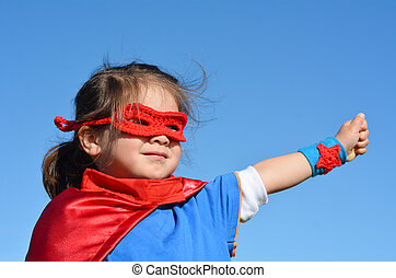 Superhero child (girl) against dramatic blue sky background with copy space. concept photo of Super hero, girl power, play pretend, childhood, imagination.