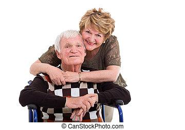 elderly wife hugging handicapped husband