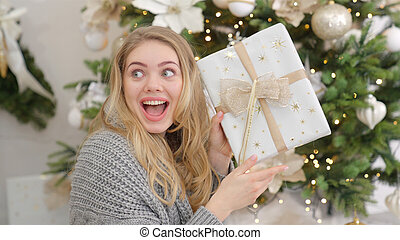 Surprised and happy young woman with christmas present box near christmas tree.