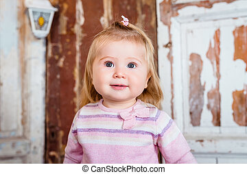 Surprised funny blond little girl with big grey eyes