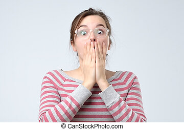 woman covering mouth with hand and staring at camera