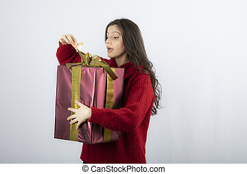 Surprised woman in red sweater opening a box of Christmas present
