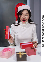 surprised woman in santa had opening Christmas gift box