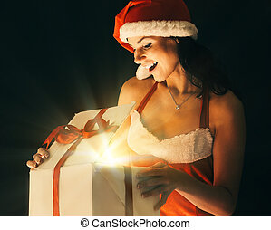 surprised young woman in costume of Santa Claus opening a Christmas gift.