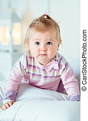 Sweet blond little girl with big grey eyes and plump cheeks