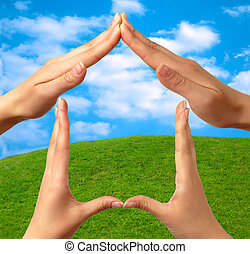 Female hands showing home sign family house concept sky grass background