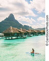 Tahiti Bora Bora beach vacation luxury hotel resort in French Polynesia. Woman paddleboarding doing watersport leisure activity on SUP. Mount Otemanu landscape summer holiday