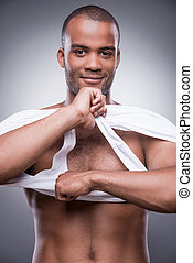 Taking his shirt away. Handsome young African man taking off his tank top and smiling while standing against grey background