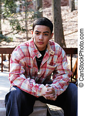 Multi-cultural teen boy wearing casual clothing; outdoor setting