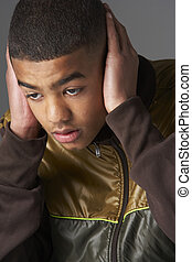 Teenage Boy Covering Ears With Hands