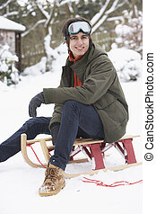 Teenage Boy With Sledge Next To Snowman