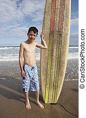 Teenage boy with surfboard
