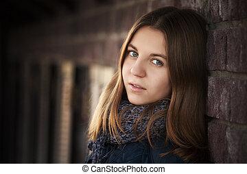 Teenage girl against a brick wall